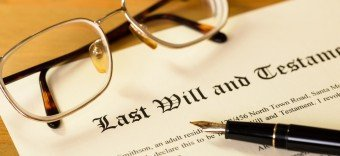 Last will and testament document with fountain pen and glasses on top constructed with the help of a professional trusts lawyer Grand Rapids