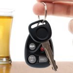 Drunk driving conceptual image with a hand holding some car keys and a glass of beer in the background.