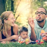 Happy interracial family is blowing bubbles. Mixed diverse family is enjoying a day in the park. Mother father and mulatto son are smiling and are picnicking in the green park.