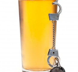 A pint of beer with a miniature pair of handcuffs holding a set of keys representing a person who got a DUI and needs help from an aggressive Grand Rapids OWI lawyer.