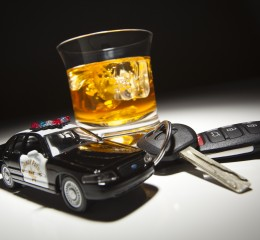 highway patrol police car next to keys and an alcoholic drink, representing drunk driving and the need for a Grand Rapids Successful OWI lawyer.