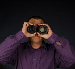 Man Looking Through Binoculars representing snooping, which should be handled with a Grand Rapids professional snooping lawyer