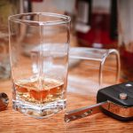 Car key on the bar with spilled alcohol and empty bottles. Booze driving concept. Drunk driver concept