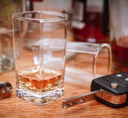 Car key on the bar with spilled alcohol and empty bottles conceptualizing the need for a dui lawyer skilled grand rapids