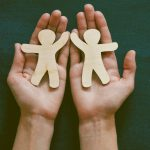 Hands holding paper dolls representing divorced parents using Grand Rapids child support modification services