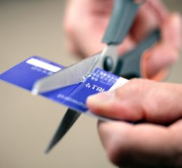 hand cutting a credit card with scissors for successful bankruptcy attorneys grand rapids