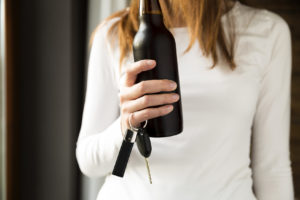 Woman holding a beer with her car keys. Contact a skilled DUI OWI lawyer to represent your drinking and driving case in Ottawa County.