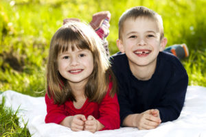 brother and sister playing outside, if seeking help with parenting time schedule consult with a skilled child custody lawyer in Grand Haven