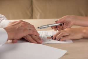 Man and woman handling divorce papers with the help of our Rockford Divorce Lawyer.