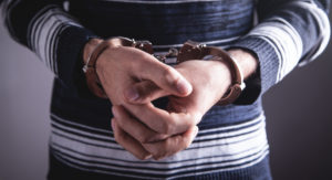 Man in handcuffs represent how our Grand Rapids Criminal Defense Lawyer can help those facing criminal charges.
