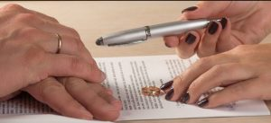 Man and woman signing divorce papers with ring on the table