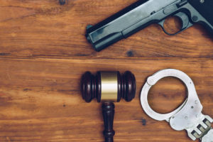 gun, handcuff and gavel on a wood surface