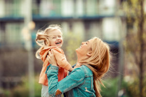 A mother shares a happy photograph of her and her daughter at a park. to a Grand Rapids family law attorney.