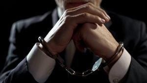 A handcuffed man sitting waiting on lawyer, contact our Grand Haven Criminal Defense Attorney for assistance.