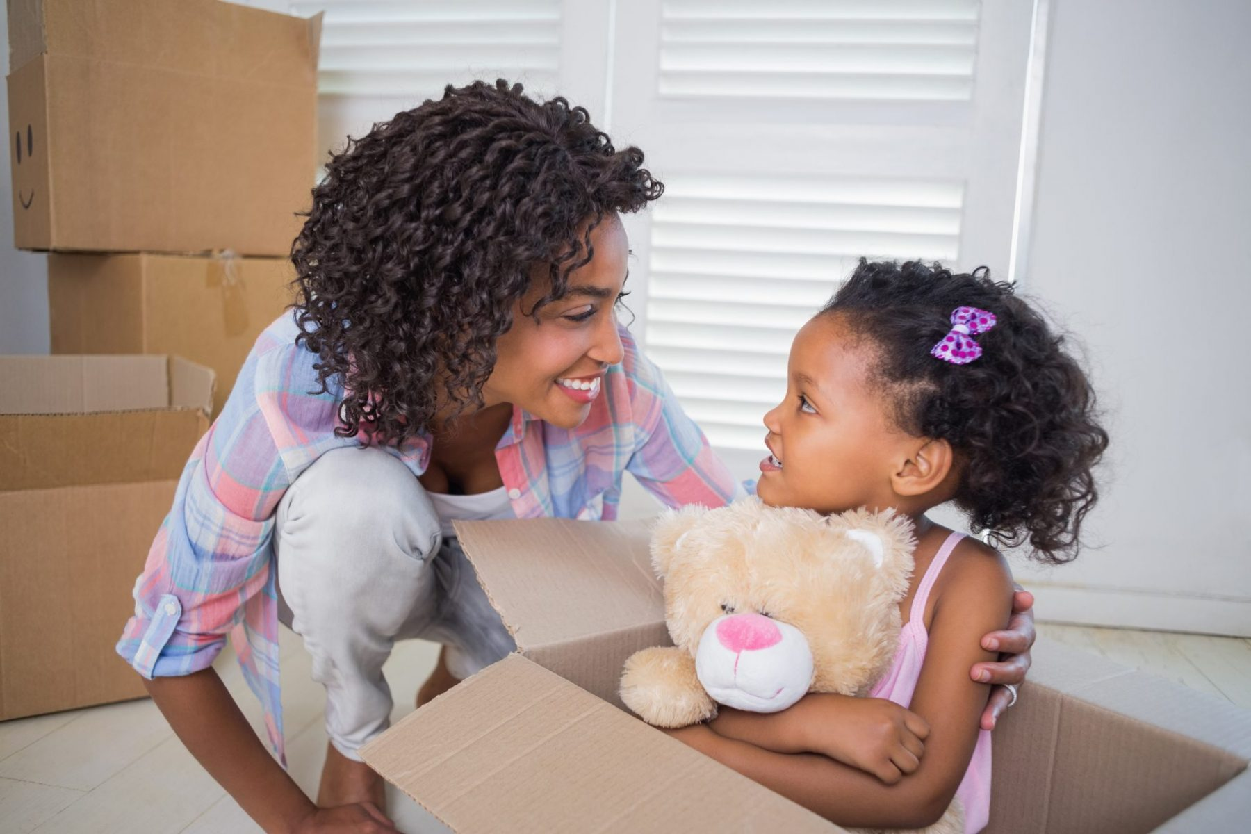 Mother and her daughter preparing for a move with boxes, for help with your parenting agreement speak to our Parenting Agreement Modification Lawyer Michigan.