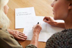 A woman helping her mother complete her last will, see a professional Estate Planning Attorney in Michigan for official will filing.