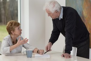 An older man showing divorce papers to his wife, consult with Divorce Lawyer by Grand Rapids for guidance with your gray divorce.