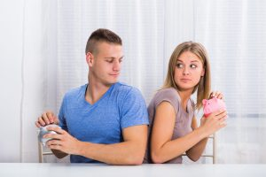 A couple putting money in their piggy bank behind each other's backs, when dividing marital property talk with a valuable divorce lawyer in Grand Rapids.