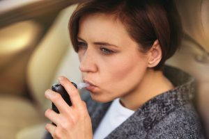 A woman using a breathalyzer sitting in her car, a drunk driving defense attorney Grand Rapids could be able to help you through your DUI arrest.