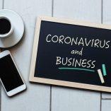 Coronavirus and Business text written on blackboard. COVID-19 - Wuhan Novel Coronavirus pneumonia. Chalk board with coffee and mobile phone for the Grand Rapids Lawyer Van Den Heuvel.