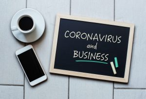 Coronavirus and Business text written on blackboard. COVID-19 - Wuhan Novel Coronavirus pneumonia. Chalk board with coffee and mobile phone for the Grand Rapids Lawyer Van Den Heuvel.