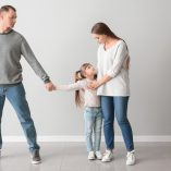 A family going through divorce, with child holding hand of father while hugging on to mother, for child custody modifications speak to Grand Rapids family law attorney.