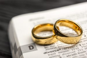 Two rings laying on dictionary definition of divorce, when needing the best Grand Rapids Divorce Lawyers.