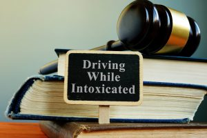 Drinking and driving concept with law books, consult with skilled Grand Haven DUI Lawyer when charged in DUI accident.