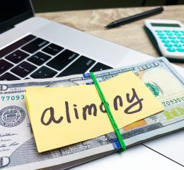 "A laptop with money and a post-it note that says ""Alimony"" on top, representing how one can benefit from calling a Grand Rapids family law attorney."