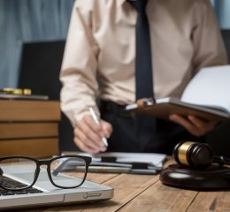 A lawyer in his office with a laptop open, reading some notes and a lot of books on his desk, representing how one can benefit from calling a Grand Rapids DUI lawyer.