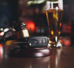 A gavel and set of car keys sitting in front of a glass of beer, representing how a Grandville, MI OWI lawyer from our firm can represent your OWI case.