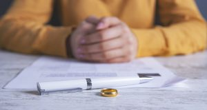 Woman with hands folded over divorce papers with a pen and wedding ring in focus in front of her, representing how our Grand Rapids divorce lawyers can assist you in your divorce.