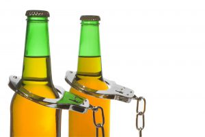 Two beer bottles with handcuffs on them for drunk driving arrest contact our experienced Grand Rapids DUI lawyers.