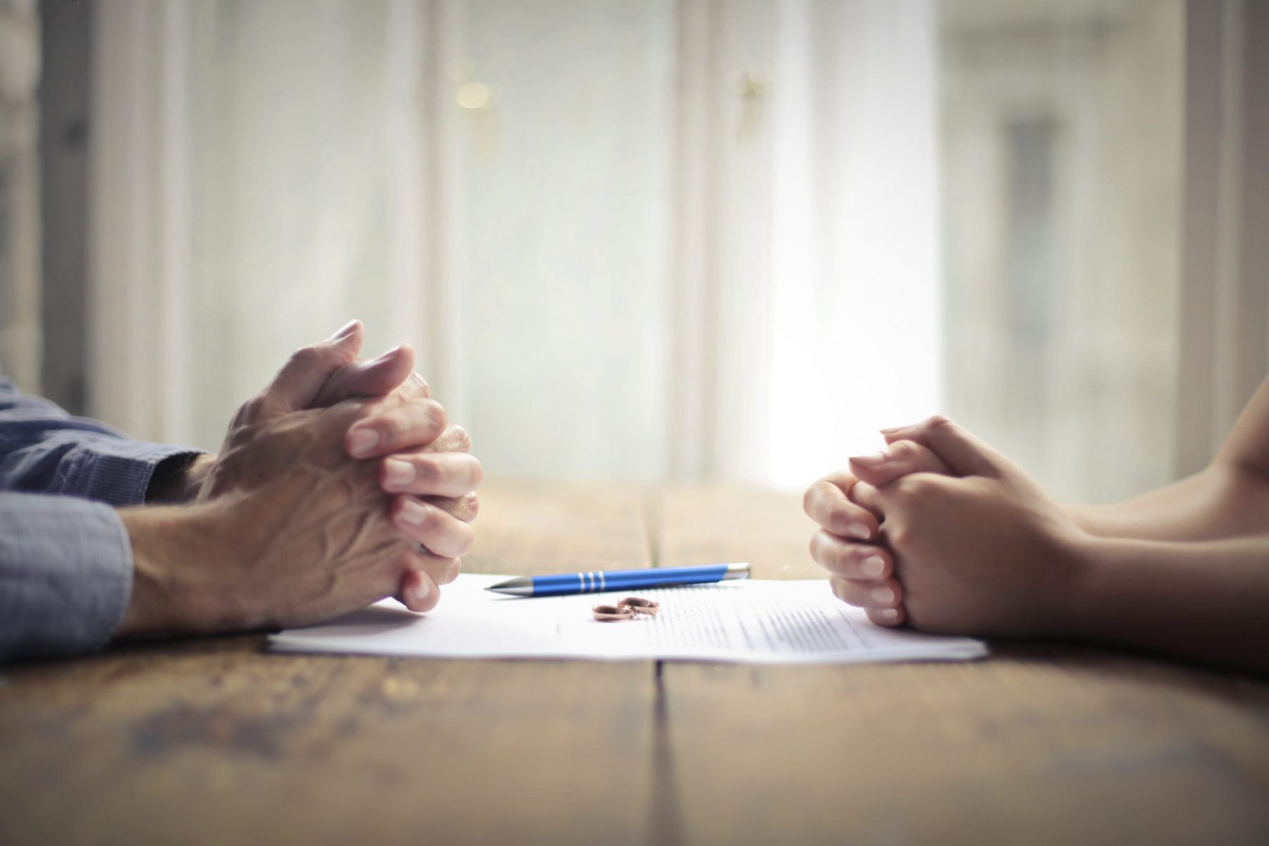 A man and a woman with their hands folded and rings, a pen, and papers on a table representing the need for a Grandville divorce attorney.