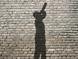 Shadow of person drinking against brick wall, when arrested for public intox, seek the guidance of a good Michigan Criminal Defense Law Firm.