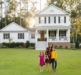 A woman with her two daughter standing outside their home, for help with dividing assets with your divorce talk to Property Division Lawyer Grand Rapids.