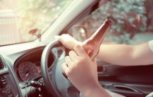 Man driving while drinking beer representing how a Caledonia DUI Attorney can help you if you get a DUI in Michigan
