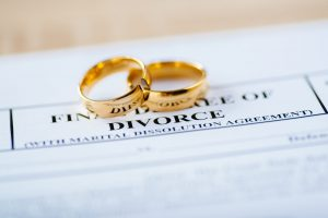 "Wedding rings on divorce papers representing how a ""divorce lawyer near me"" can help your case"