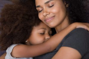 A mother and daughter hugging representing how our Grand Rapids child custody lawyer can help with your child custdoy case.