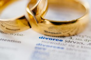 Two gold wedding rings on top of a dictionary open to the definition of the word divorce representing how our Michigan divorce attorneys can assist you with your case.